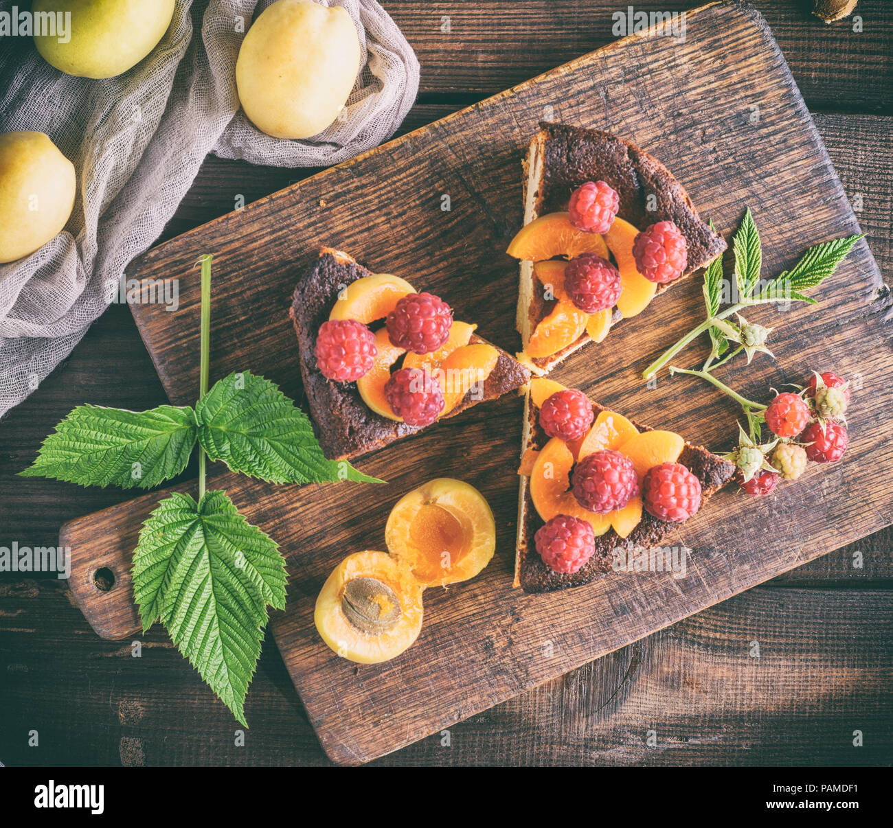 pieces of cottage cheese pie with strawberries and apricots on a brown wooden board, top view - Stock Image