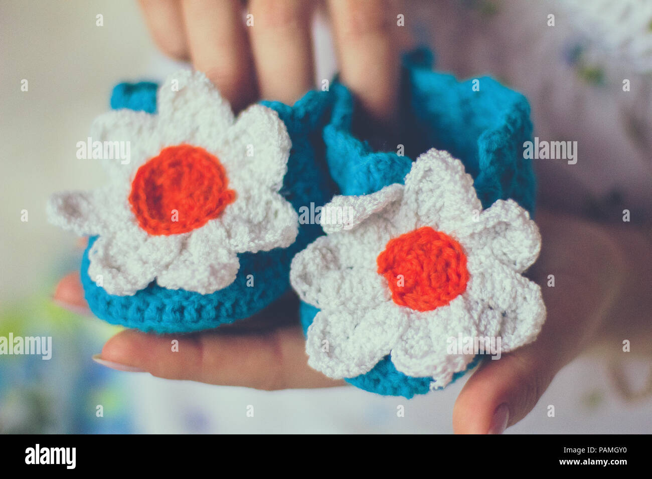 Baby knitted slippers in hands - Stock Image