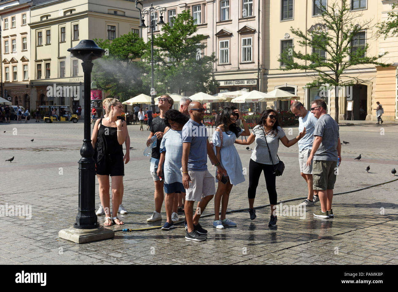 People cooling down in the spray of water mist as temperatures soar into the thirties in Krakow Poland 2018 - Stock Image