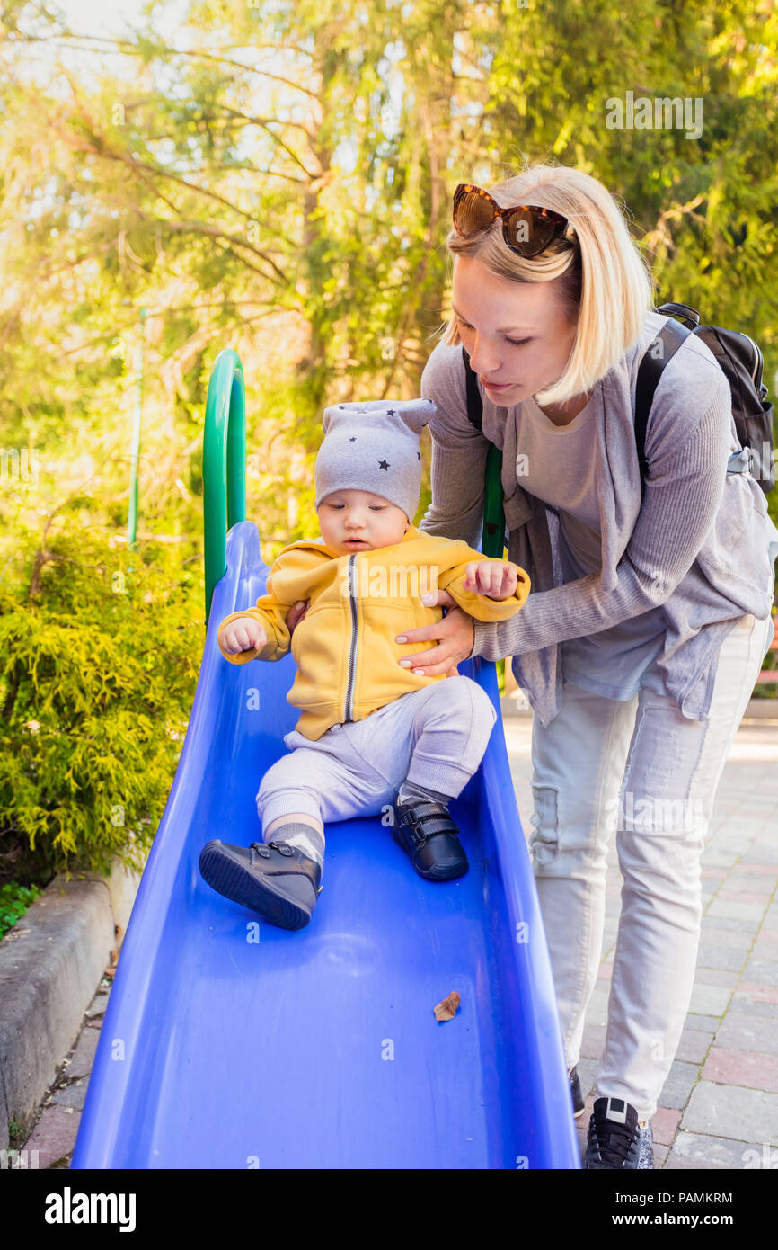 Mom and son ride the slide on the playground - Stock Image