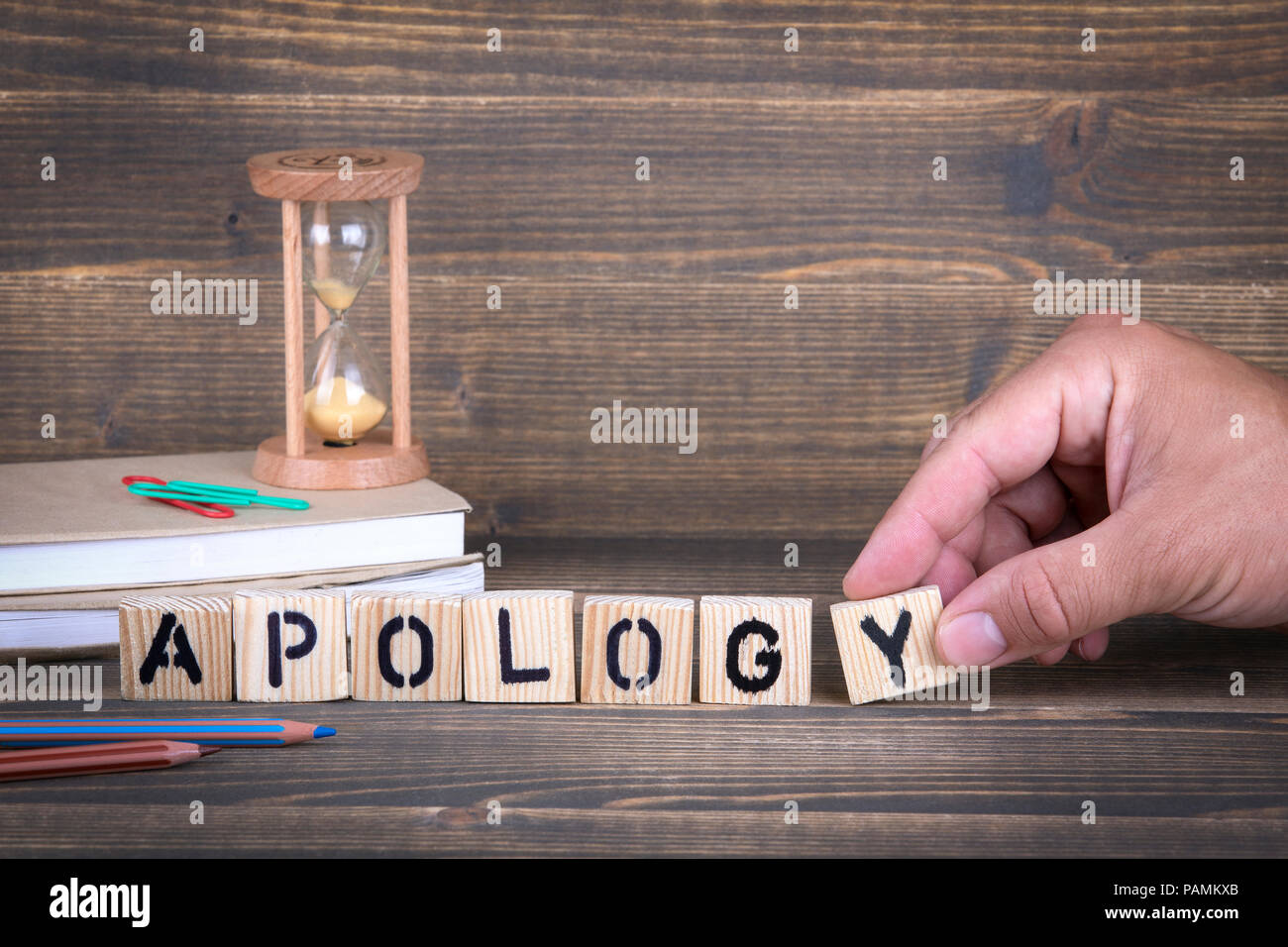 Apology. Wooden letters on the office desk - Stock Image