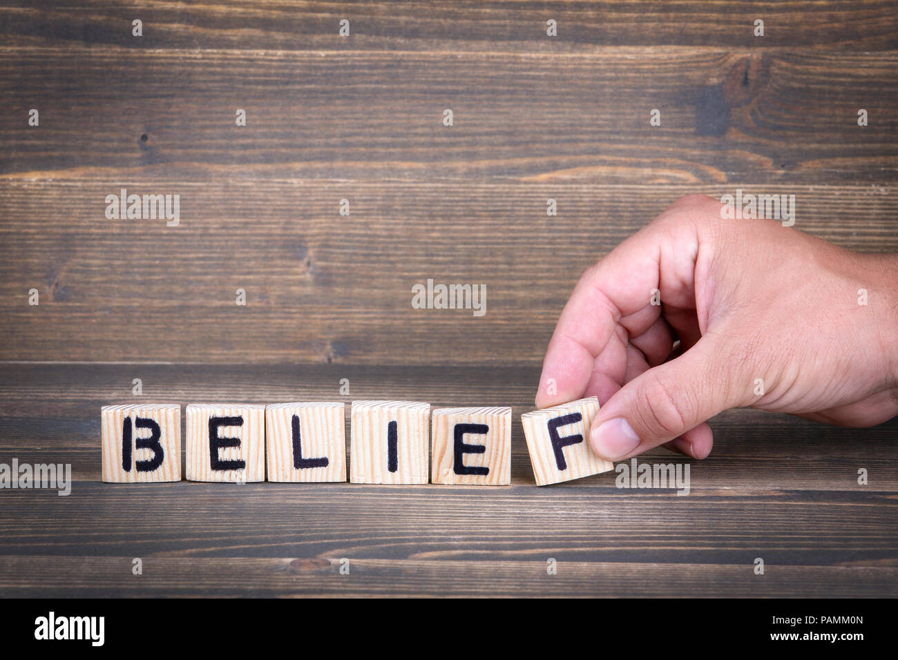 Belief. Wooden letters on the office desk - Stock Image
