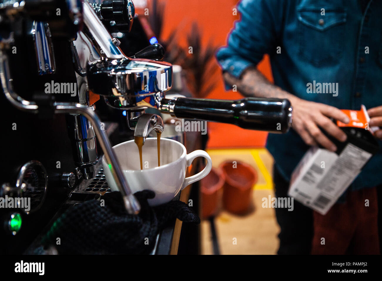 Fancy stainless steel coffee machine pouring a double espresso in a coffee shop - Stock Image