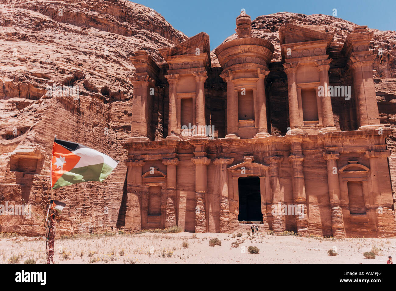 the Jordanian flag flies in front of the Monastery, one of the largest structures in the Lost City of Petra Stock Photo