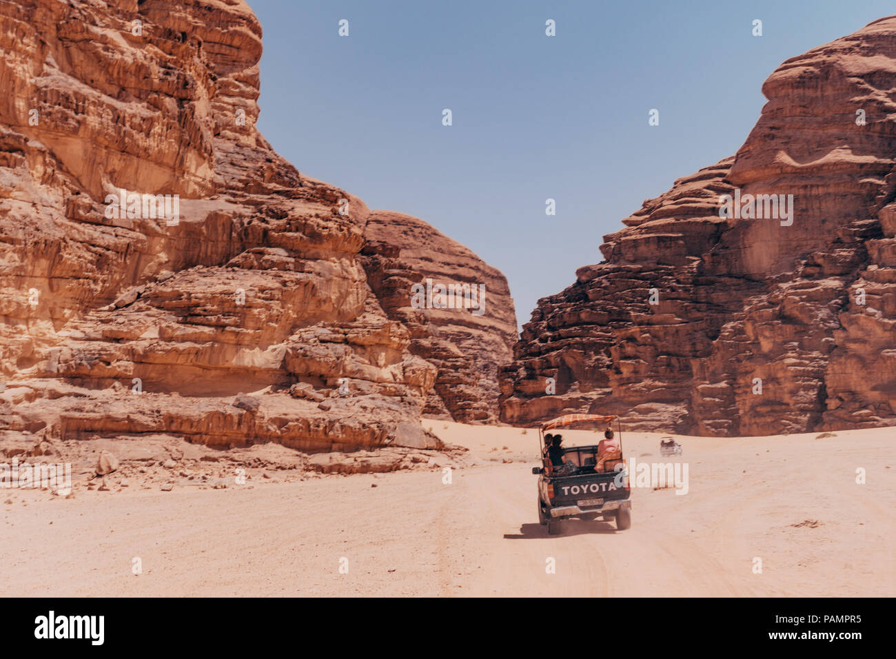 pickup tricks full of tourists drive in a convoy across the red desert sands in the famous Wadi Rum National Park, Jordan - Stock Image