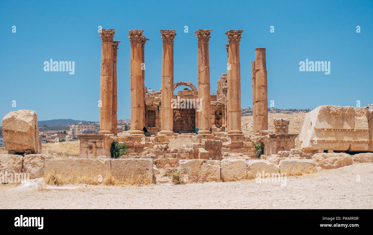 old ancient Greco-Roman columns line cobblestone streets on a warm summers day in Jerash, Jordan - Stock Image