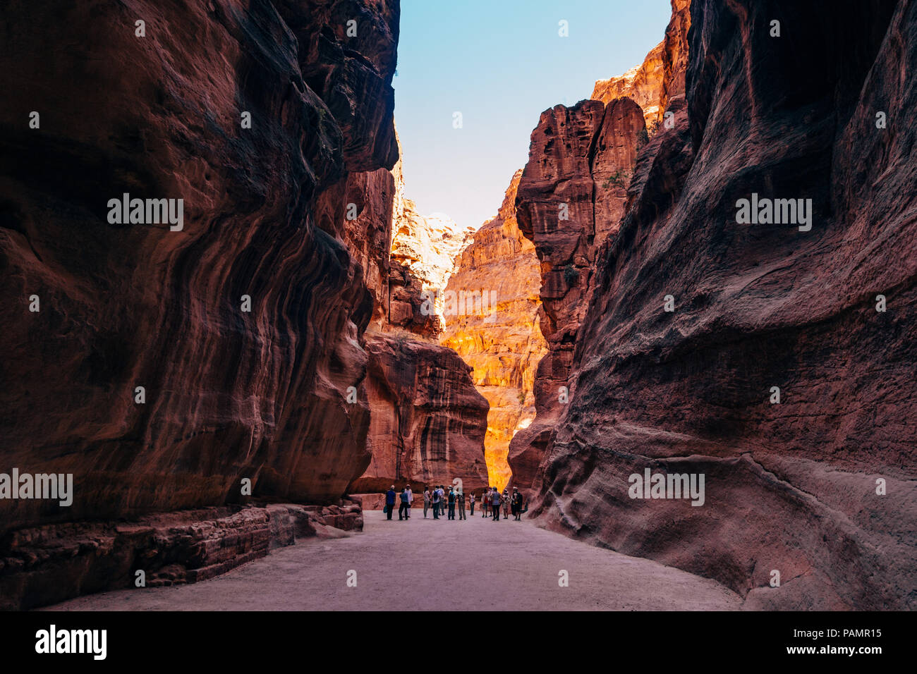 a tour group walks down the main path into Petra, Jordan. The canyon was carved by the rock splitting during an earthquake - Stock Image