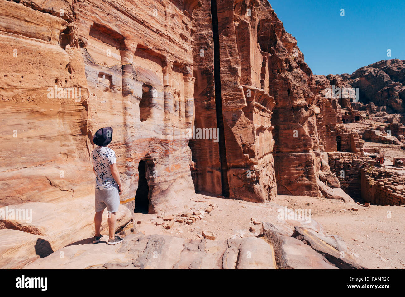 a tourist poses on a rock ledge looking over a tomb entrance in the Lost City of Petra, Jordan - Stock Image