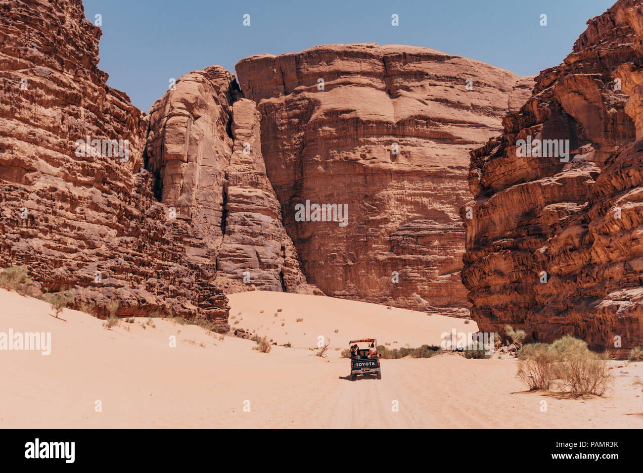 a Toyota pickup is dwarfed as it drives between the enormous rock formations in Wadi Rum National Park, Jordan - Stock Image