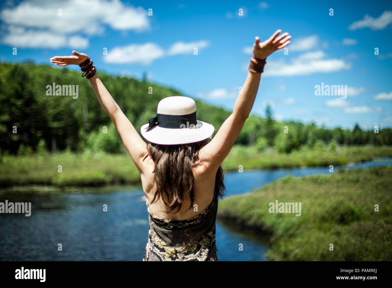 Woman wearing summer hat with her arms up enjoying a beautiful sunny day by the river, seen from behind Stock Photo