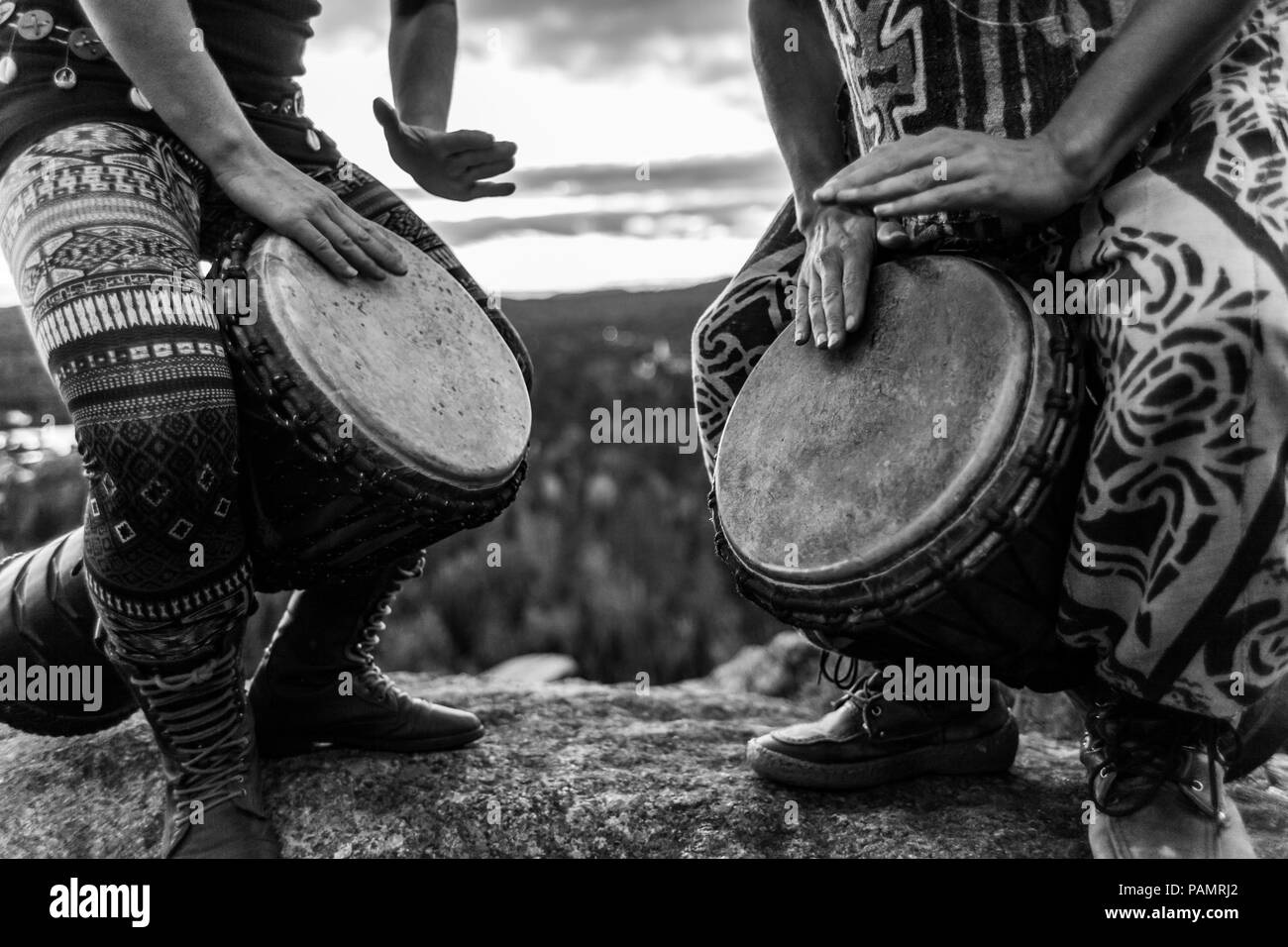 Man and woman playing djembe on the top of a mountain black and white