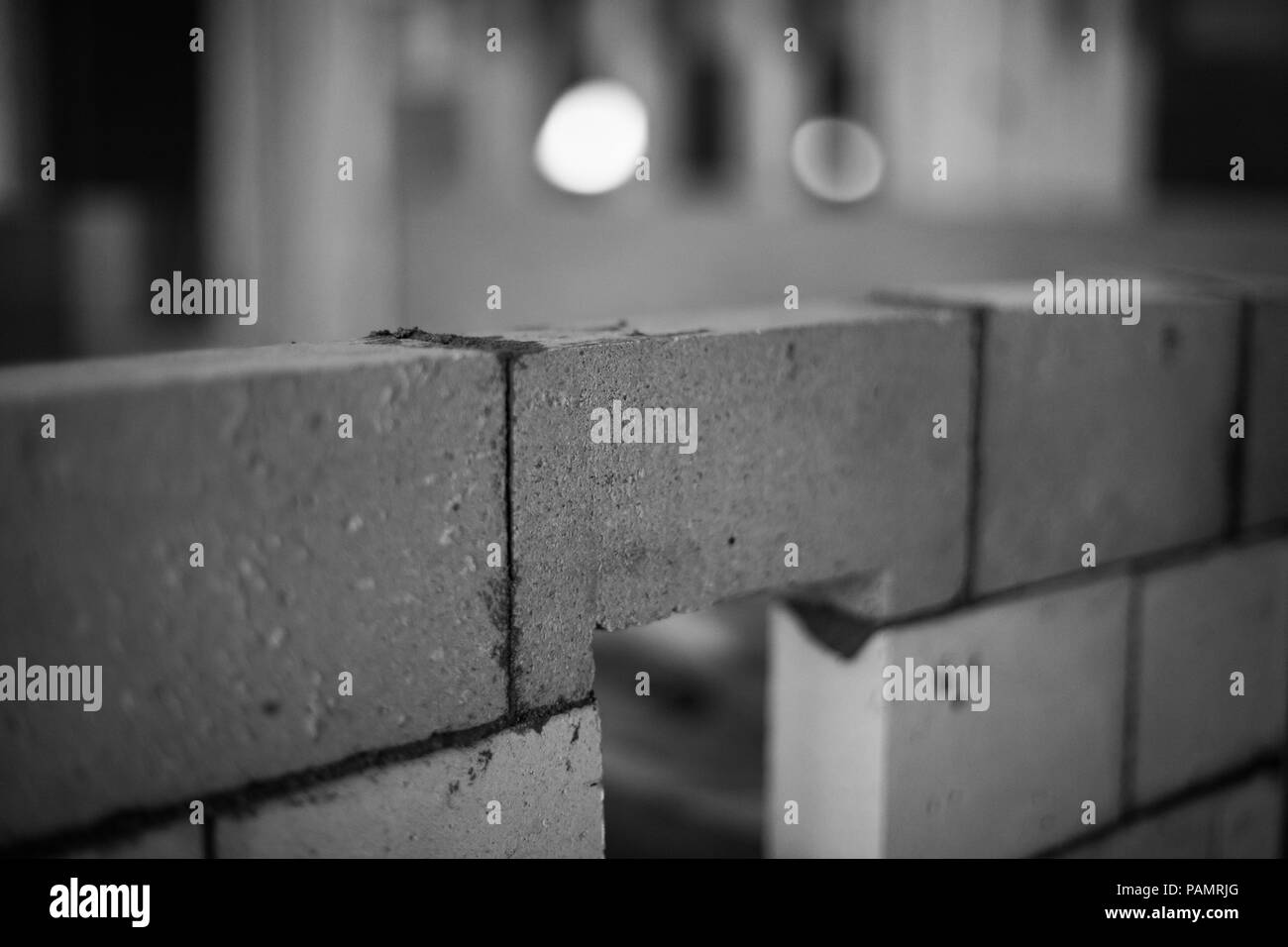 Close up of a brick with fresh cement in a brick wall, black and white - Stock Image