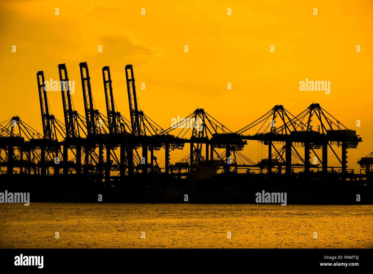 Singapore, Singapore - April 23, 2017: The mechanical cranes of Singapore's shipping port sit silhouetted during a fiery orange silhouette. - Stock Image