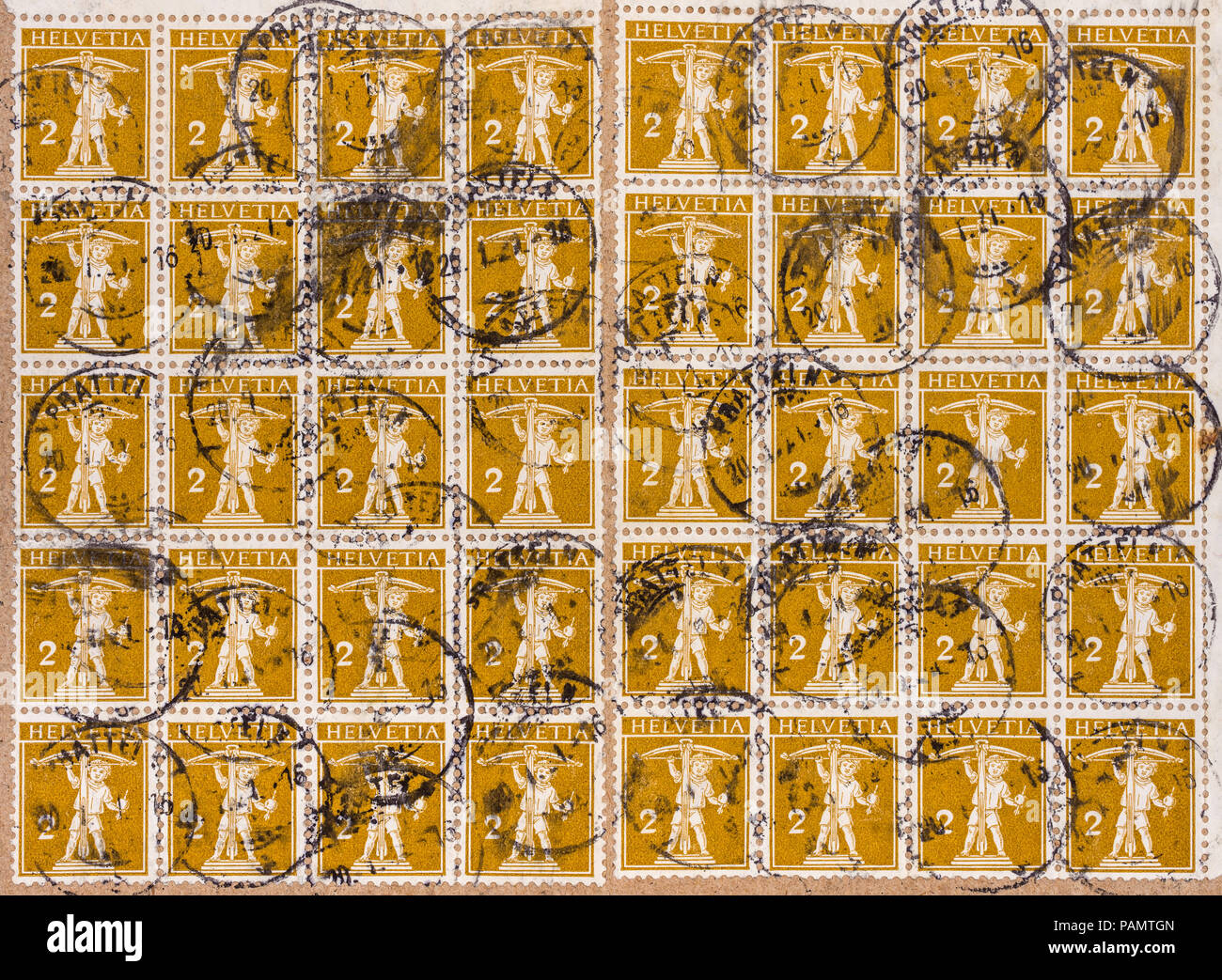 40 cancelled 2-cent Swiss 'Tell' 1910 postage stamps on parcel wrapper. - Stock Image
