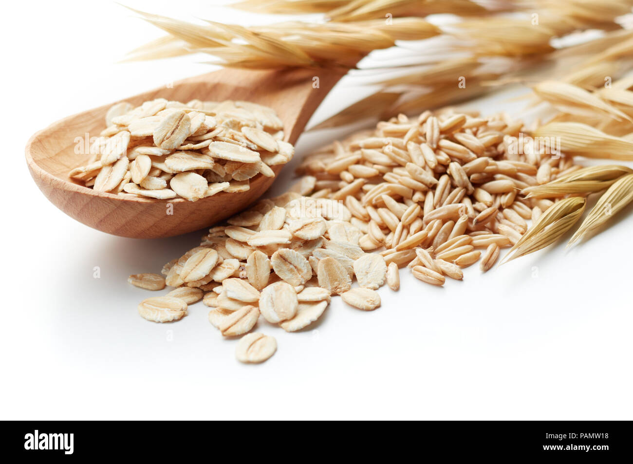 scoop and pile of oatmeal with its unprocessed grains and plant - Stock Image