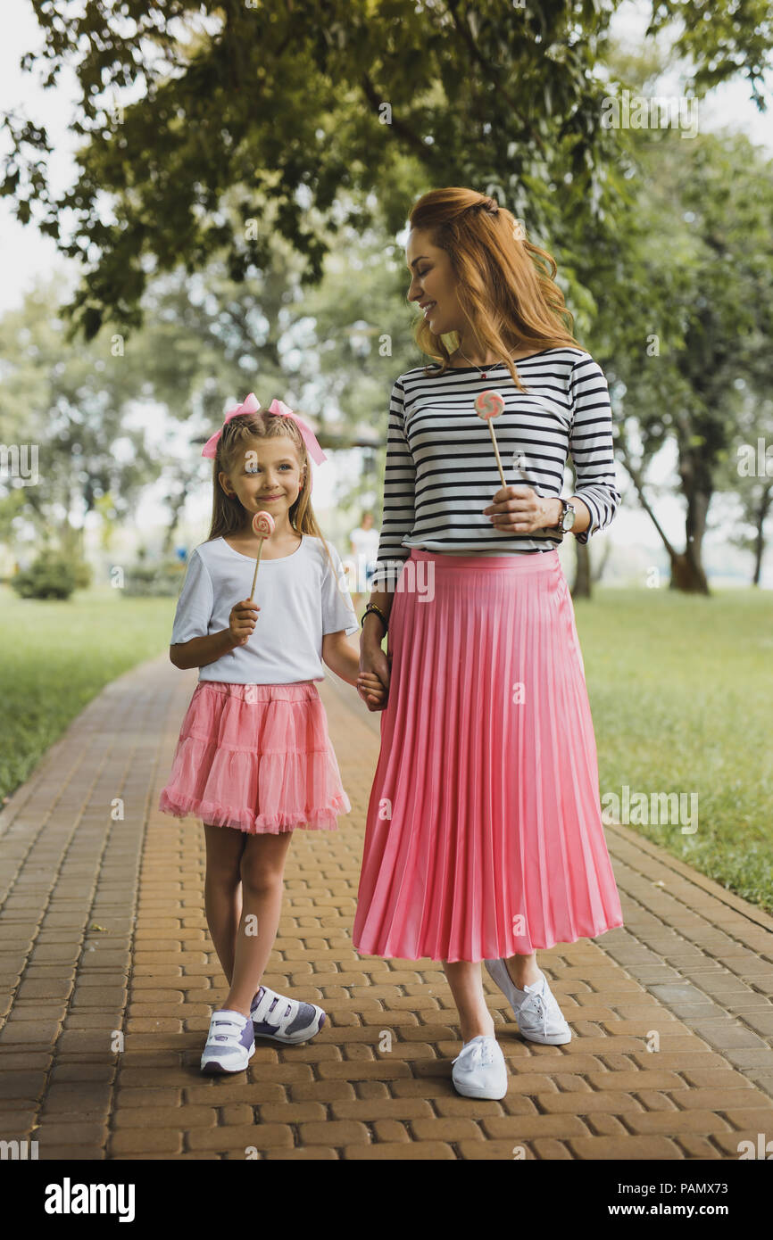 Mother and daughter wearing pink skirts and white sneakers - Stock Image