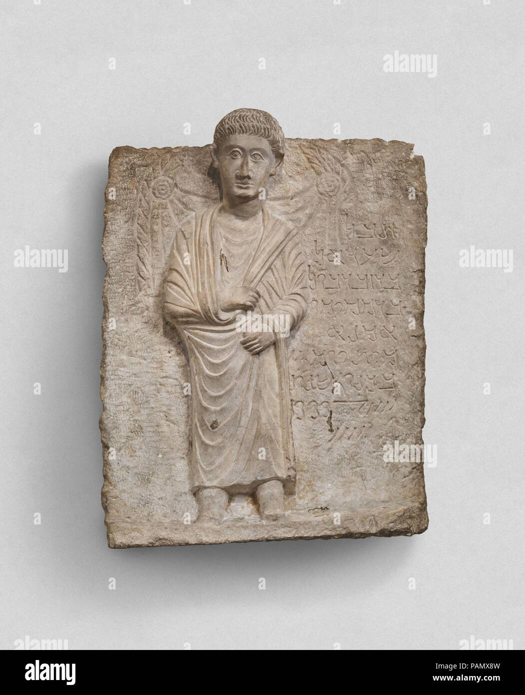 Funerary relief. Dimensions: 20.63 x 15.63 in. (52.4 x 39.7 cm). Date: ca. 172.  Inscription:  1 Alas!   2 Shu'adel,   3 son of Zabdibol,   4 son of Mokimu,   5 the craftsman.   6 Died the 3rd day   7 of Kanun, the year   8-9 484.  Transliteration:  1 hbl  2 s?d?l  3 br zbdbwl  4 br mqymw  5 ?mn?  6 myt ywm 3  7 bknwn snt  8 4.100+80  9 +4  This relief is a type of funerary monument characteristic of the prosperous caravan city of Palmyra during the first three centuries A.D. Reliefs with a representation of the deceased and a short identifying inscription were used to seal burial niches in el - Stock Image