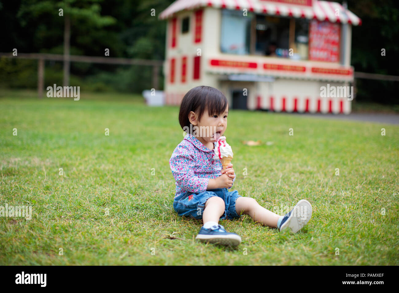 baby girl sitting on summer meadow and eating icecream - Stock Image