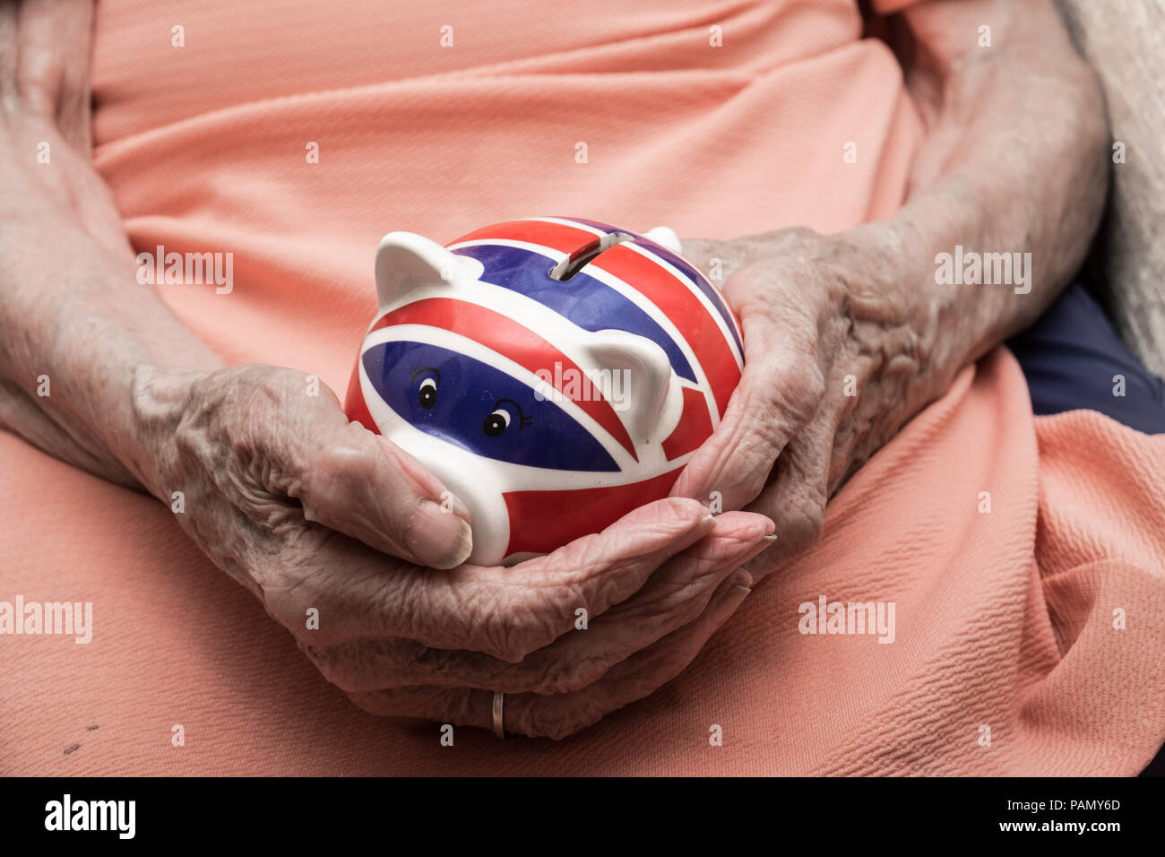 UK pension, old woman hands holding piggy bank with british flag - Stock Image