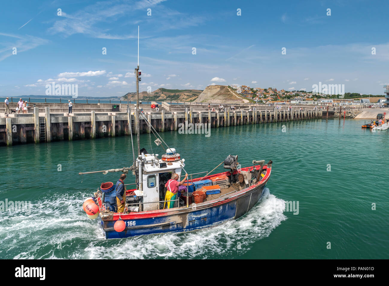 A little fishing boat returns with its catch to the picturesque harbour at West Bay in Dorset, made famous as the location for the television series ' - Stock Image