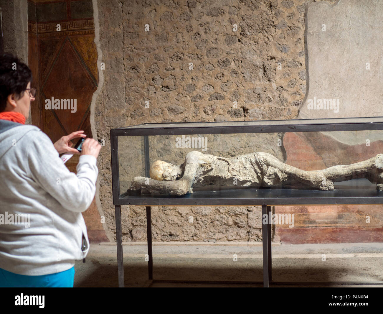 A tourist look at petrified human bodies inside the Villa of Mysteries in Pompeii, Italy. - Stock Image