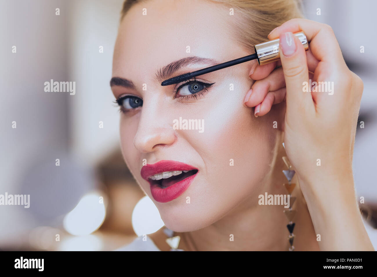 Blonde-haired woman with dental brackets coloring her eyelashes ...