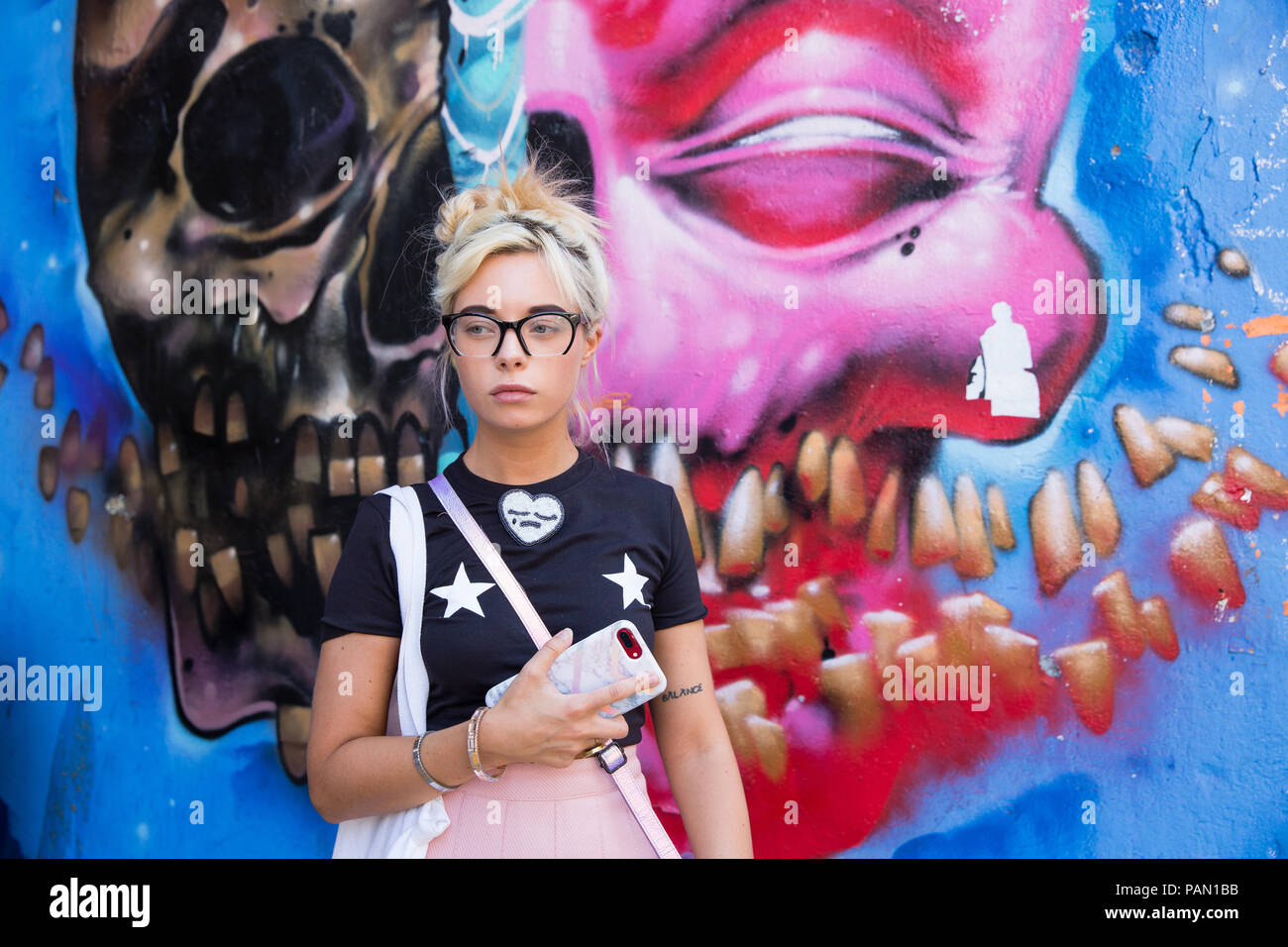 Cool Blond Hip, girl wearing a pink skirt and black short sleeved t-shirt in front of a large graffiti wall on Brick lane in Shoreditch, London, UK. - Stock Image