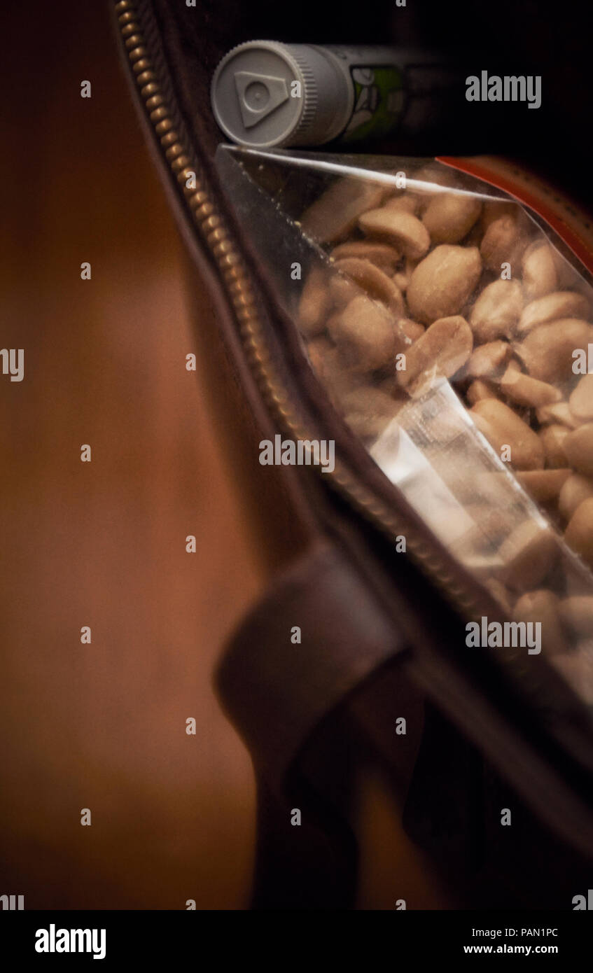 A bag with an epicene and a bag of peanuts. An artistic expression of what it is to be allergic to peanuts. - Stock Image