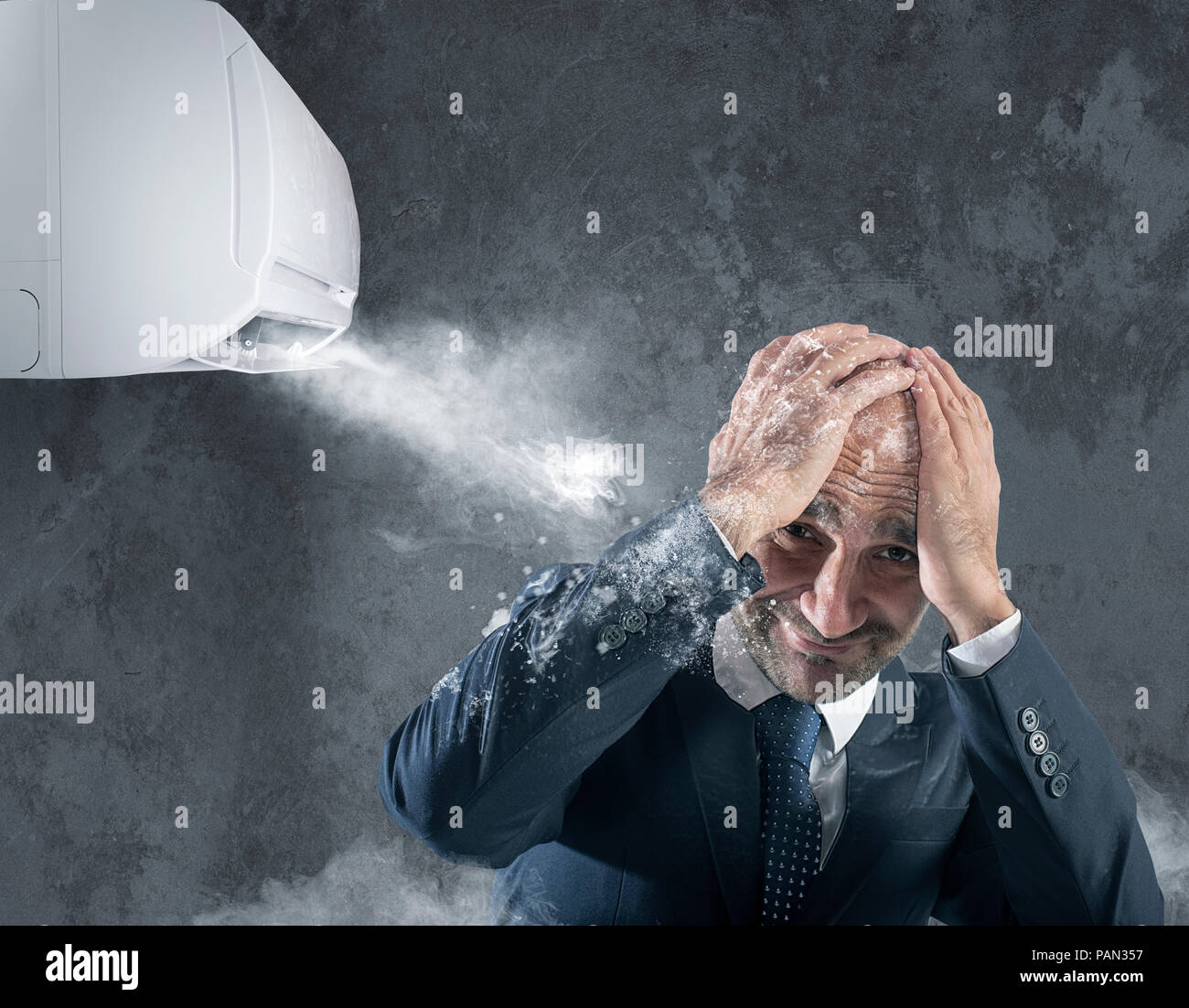 Businessman tries to protect from himself icy air conditioner - Stock Image