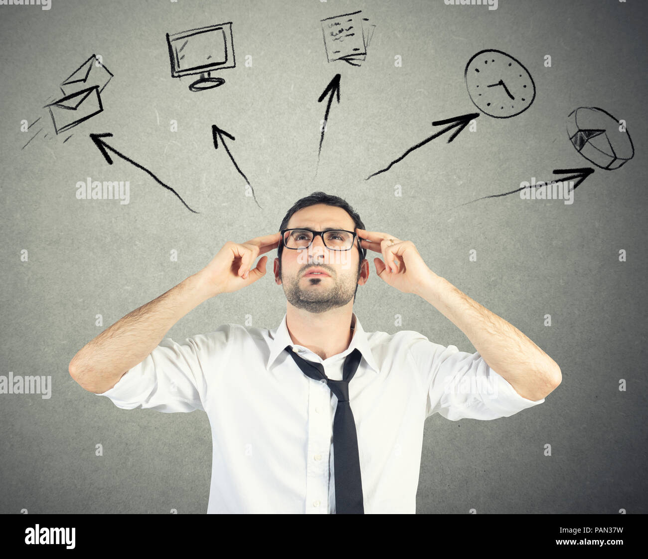 Stressed businessman tries to plan his work day - Stock Image