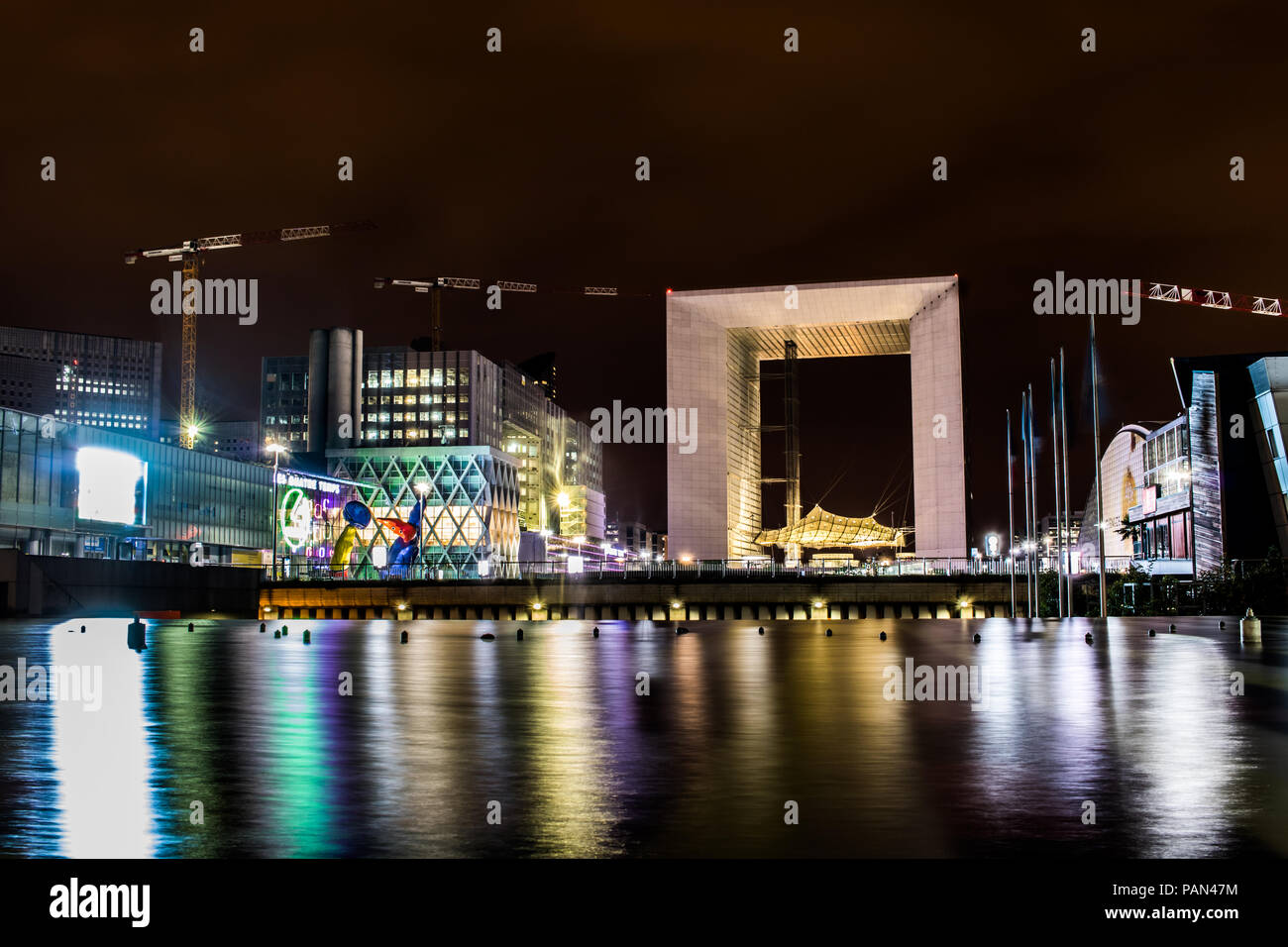 A night photo of la grande arche and the surrounding buildings in la defense the financial district in paris. - Stock Image