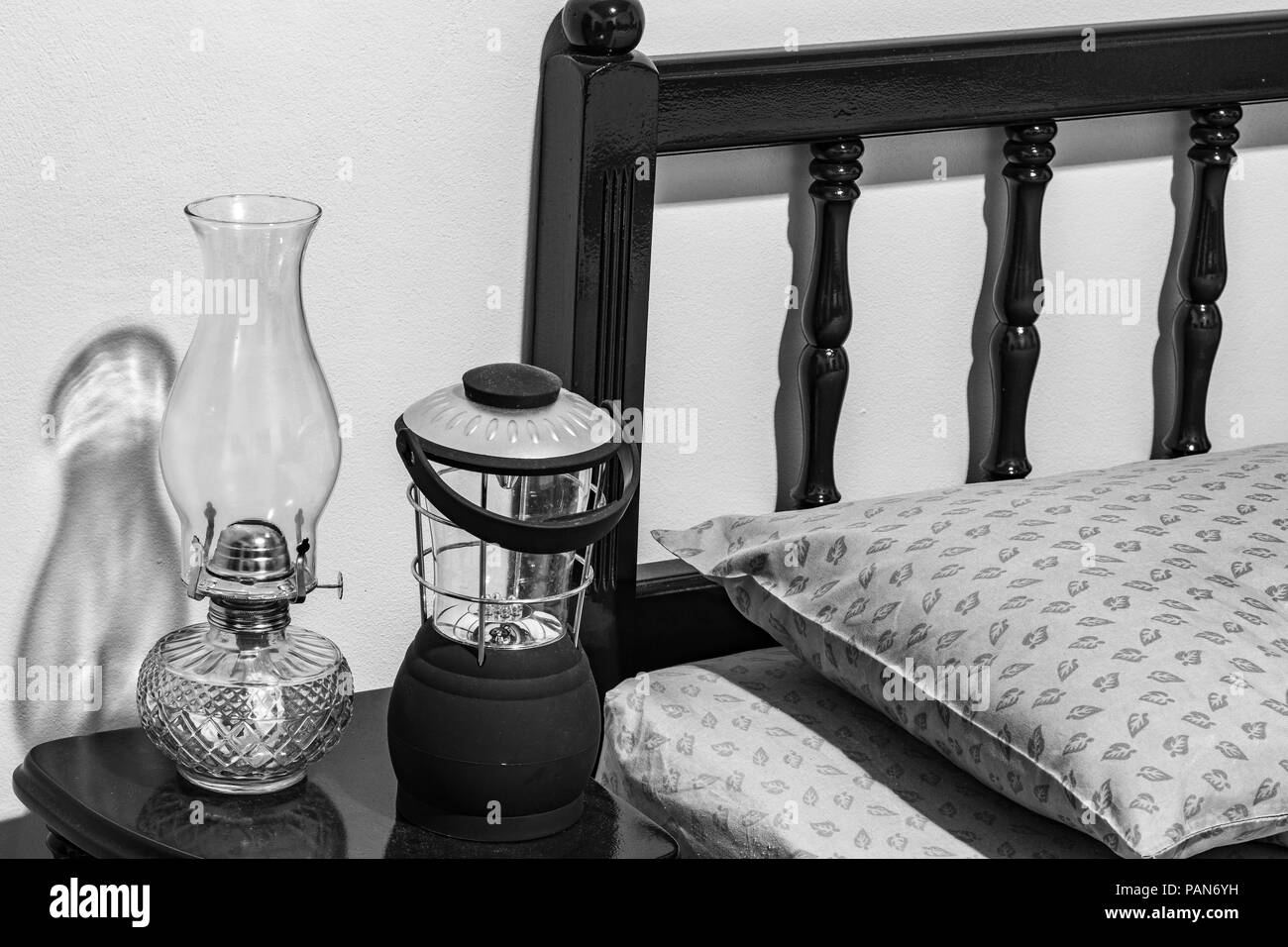 Vintage flat-wick kerosene oil lamp and modern battery operated lamp on bedside table, bed headboard, pillow, mattress, bedroom. - Stock Image