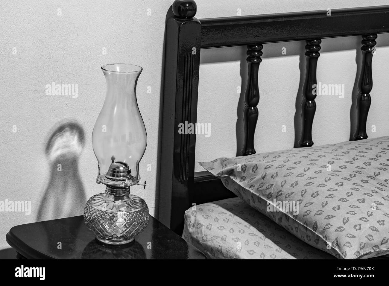 Vintage flat-wick Kerosene Oil Lamp on bedside table, bed headboard, pillow, mattress, bedroom. - Stock Image