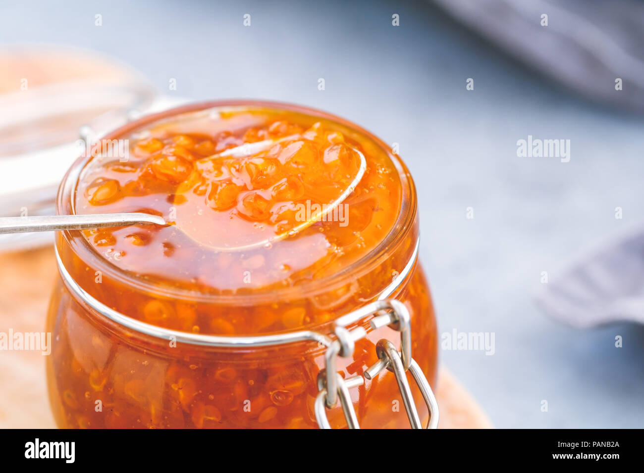 Glass jar with cloudberry jam. Nordic cuisine. Stock Photo