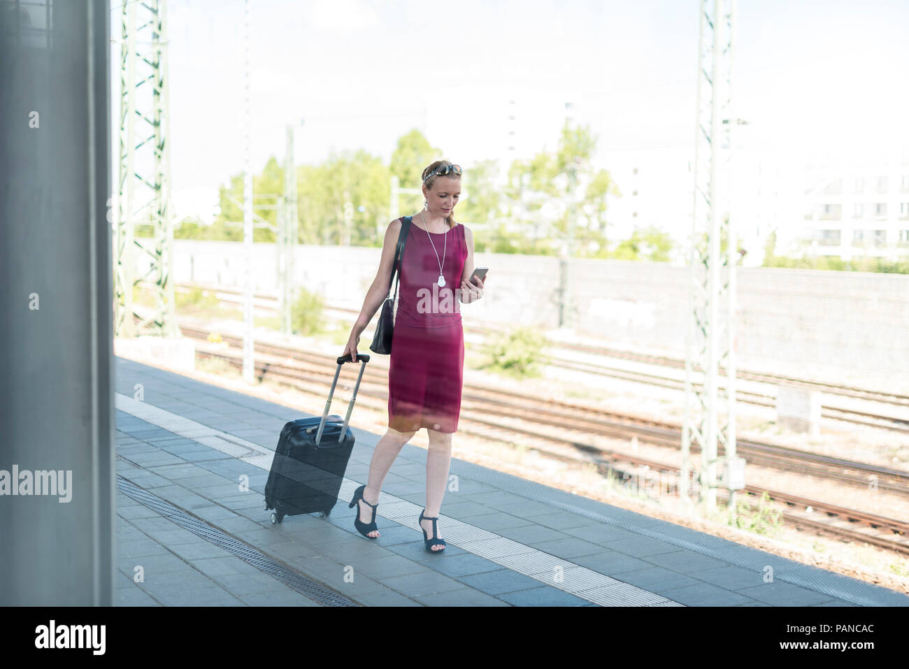 Mature businesswoman with smartphone and suitcase walking at platform - Stock Image