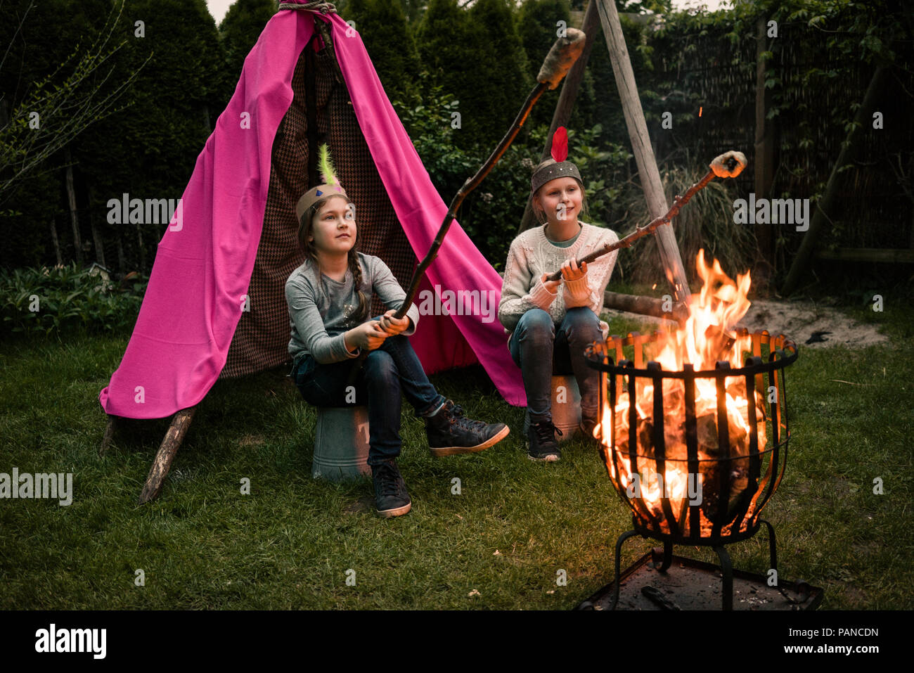 Two girls wearing feather headdress, with stock bread at camp fire - Stock Image