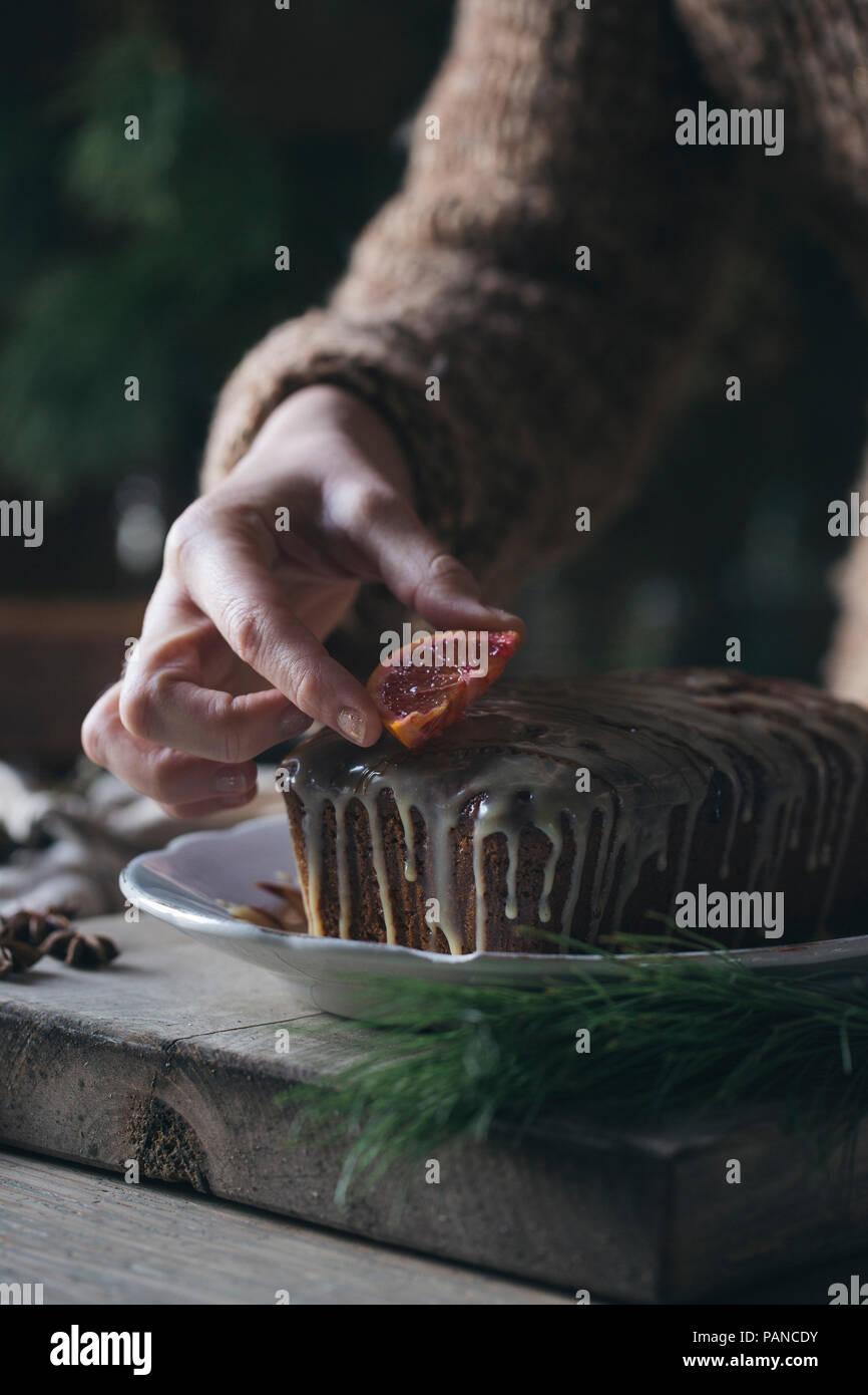 Woman's hand decorating home-baked Christmas cake - Stock Image