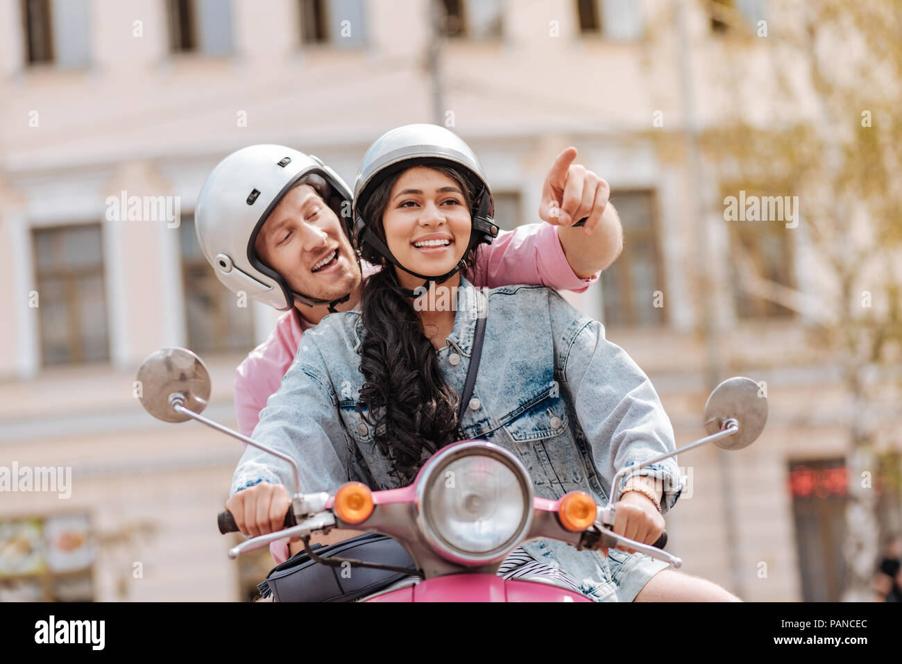 Attractive positive couple trying motorbike tour - Stock Image