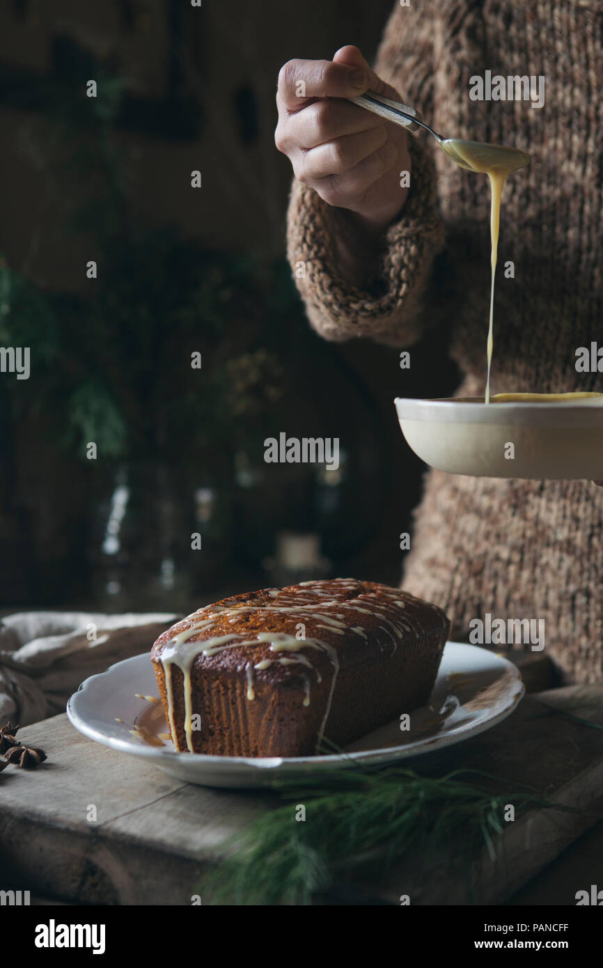 Woman preparing home-baked Christmas cake, partial view - Stock Image