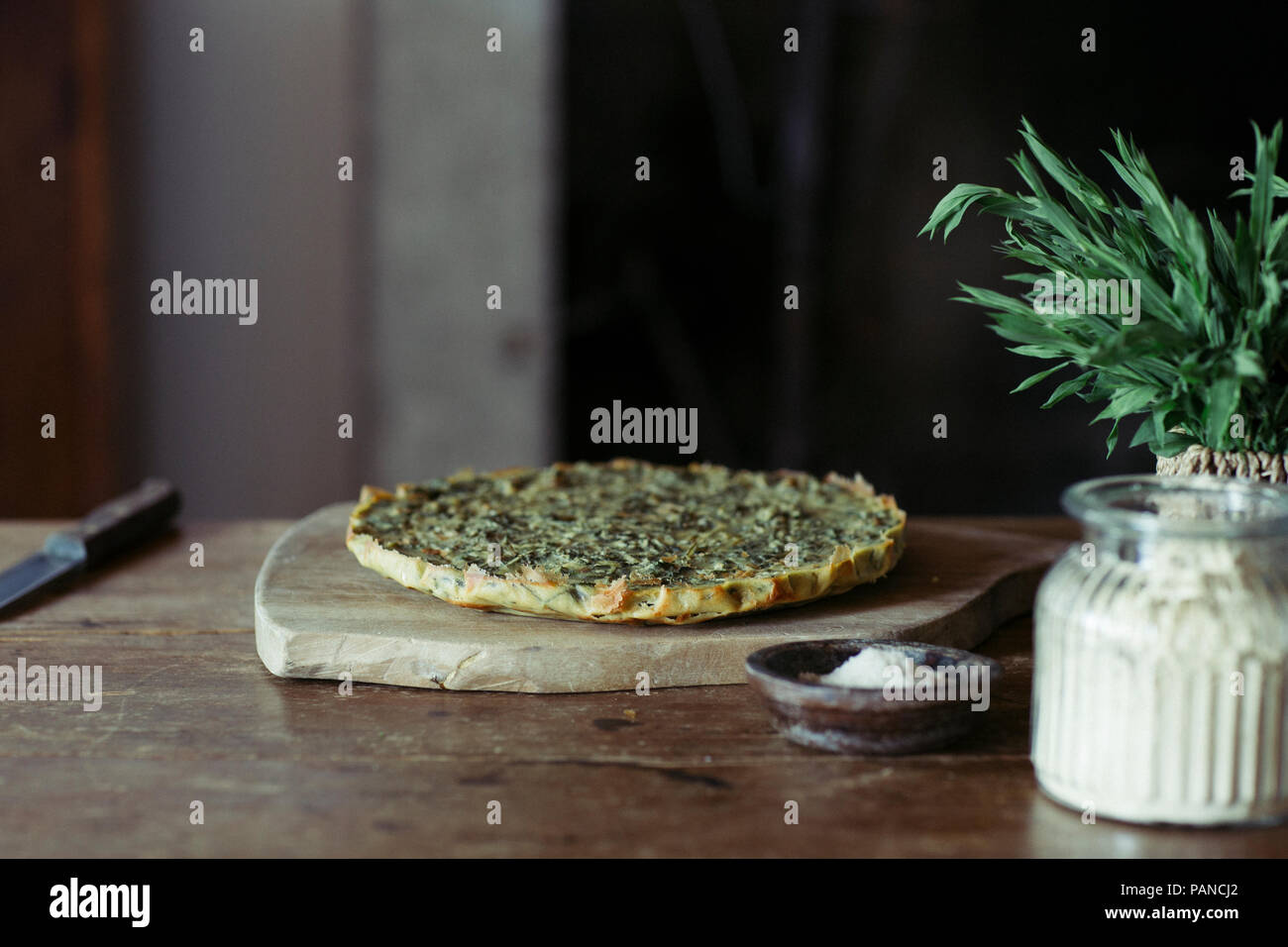 Homemade chickpea and herb cake on wooden table - Stock Image