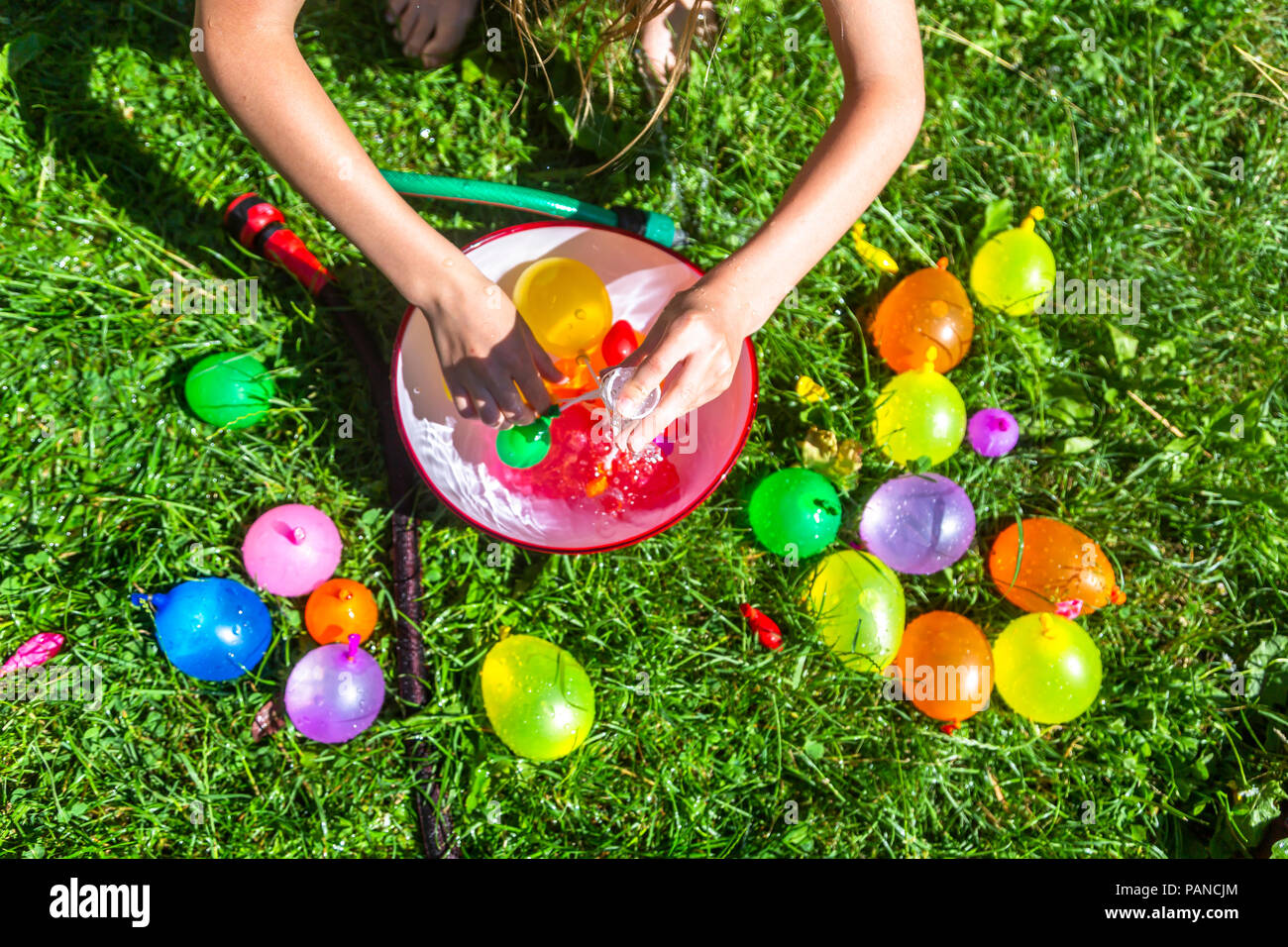 Girl preparing water bombs on a meadow - Stock Image