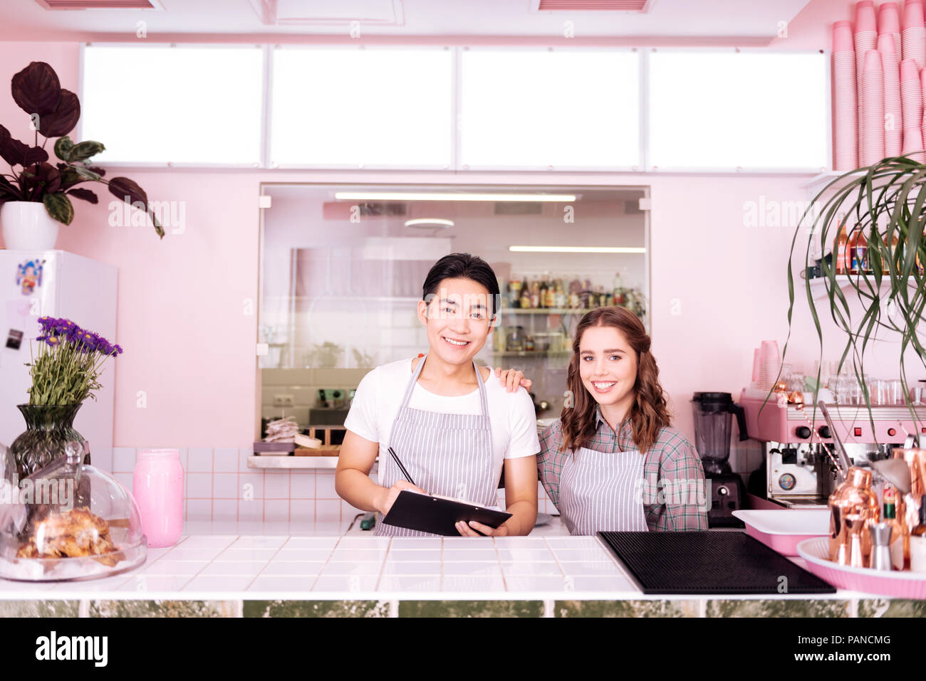 Two young smiling waiters preparing for workday - Stock Image