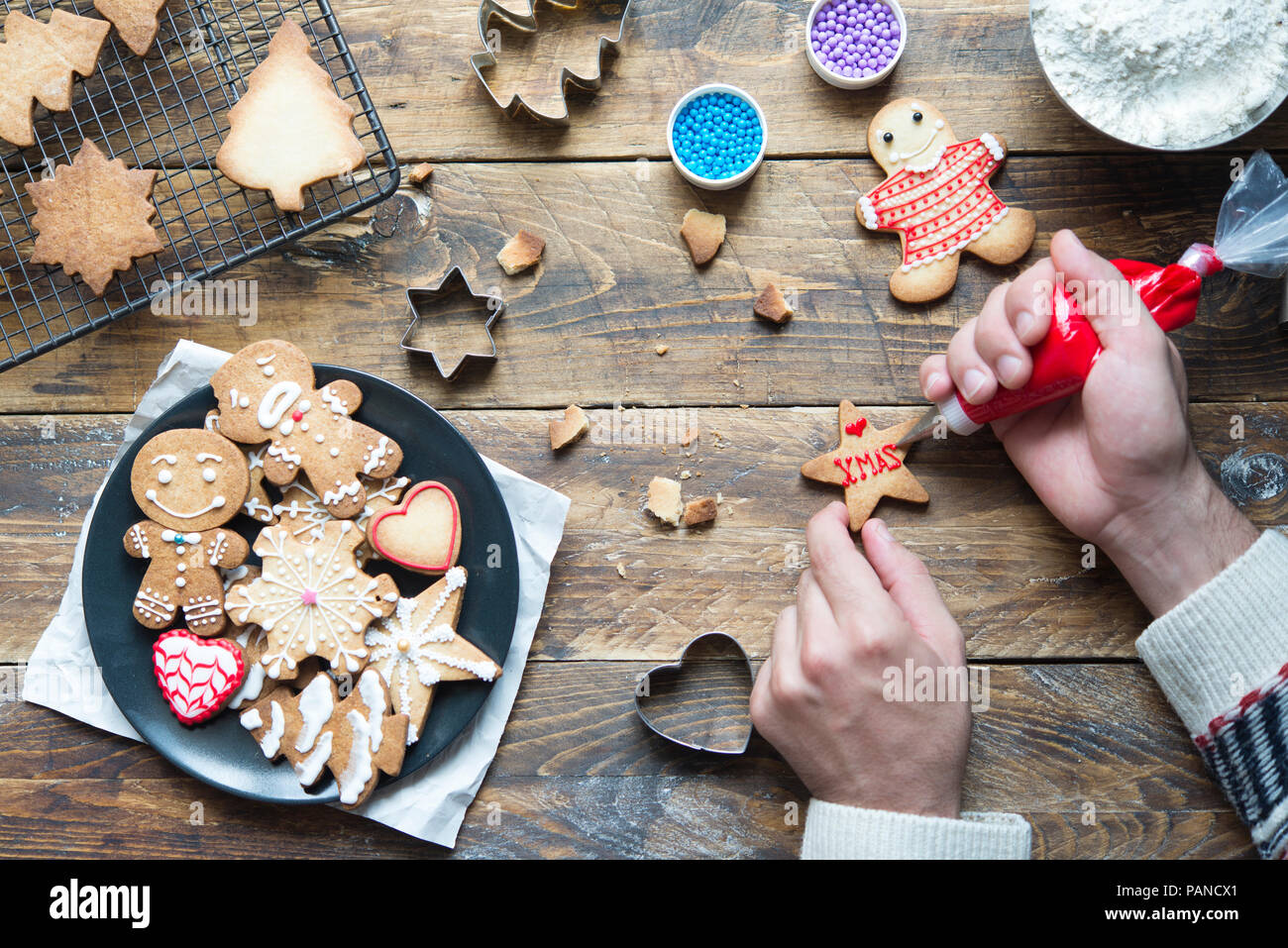 Man's hand decorating Christmas cookie - Stock Image