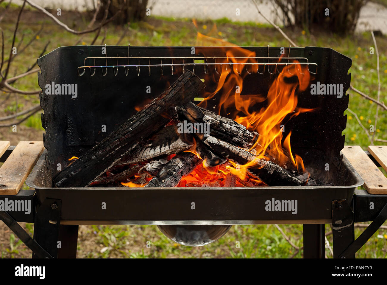 Barbecue grill with fire on nature, outdoor, close up - Stock Image