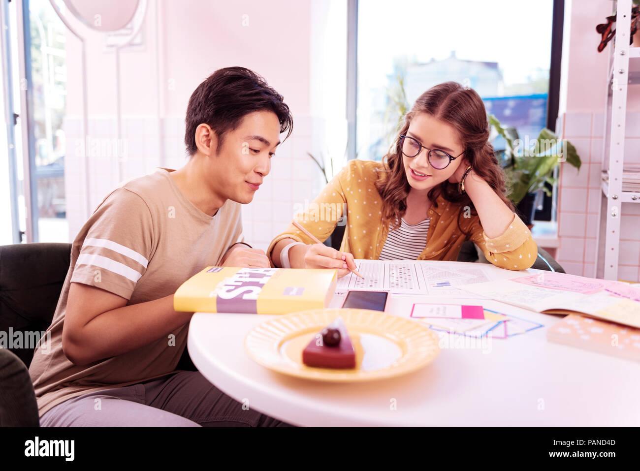 Two modern undergraduates eating cheesecake and studying - Stock Image