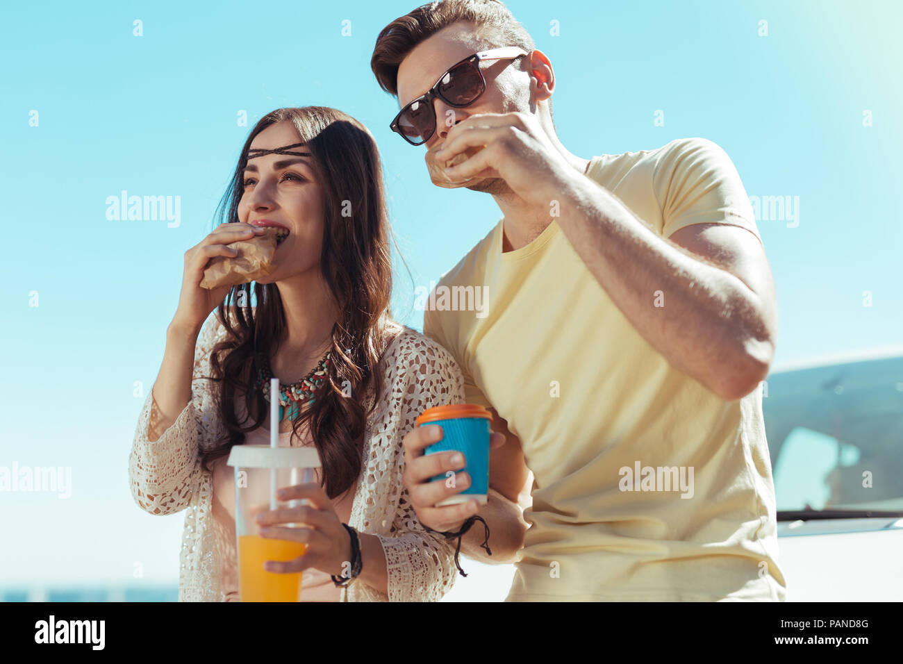 Young appealing couple enjoying tasty breakfast on fresh air - Stock Image