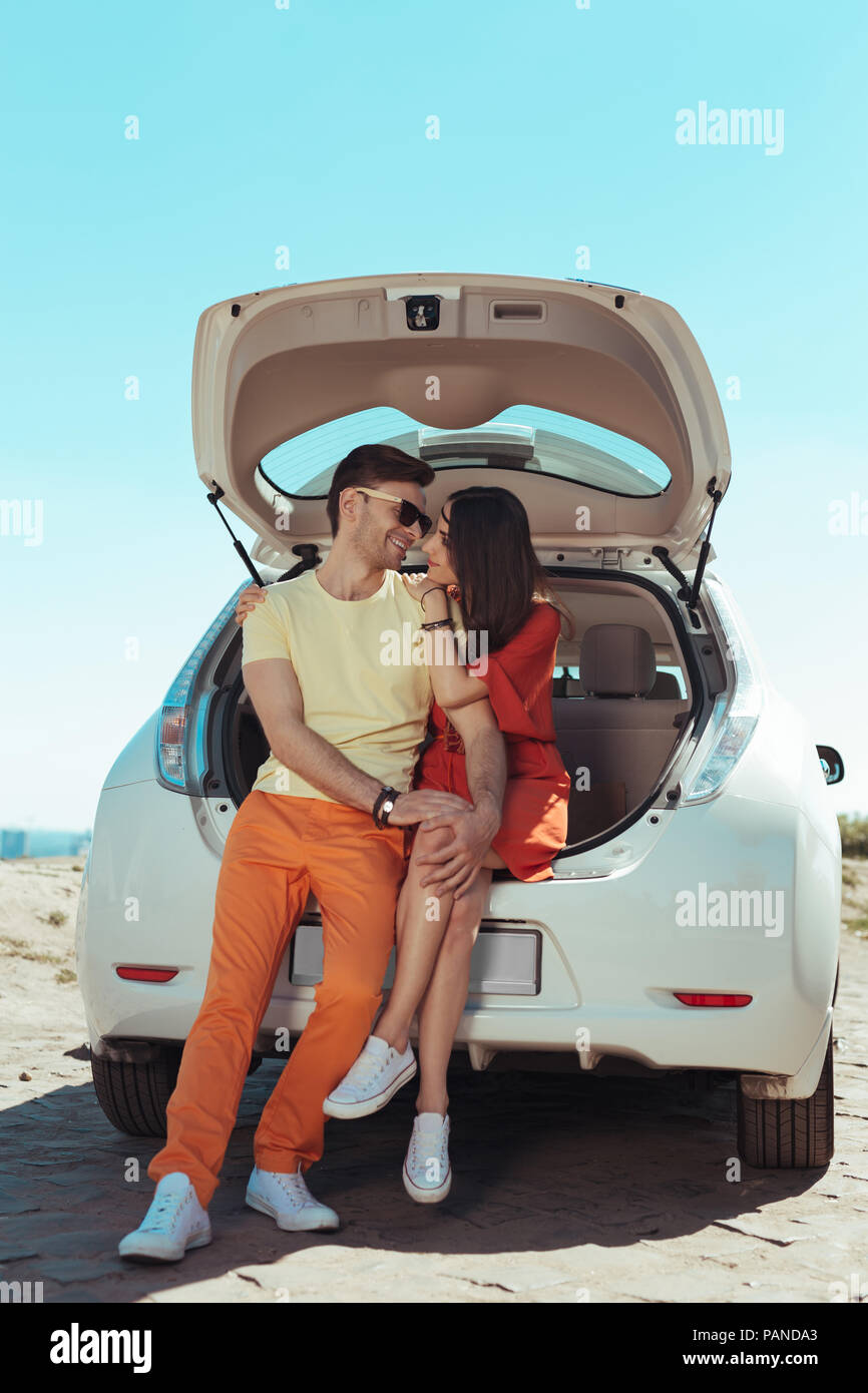 Loving couple feeling unbelievable sitting near trunk of their car - Stock Image