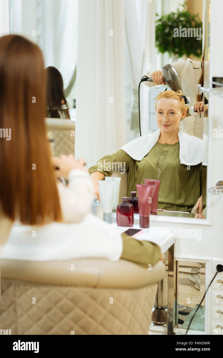Positive joyful woman looking at her reflection Stock Photo
