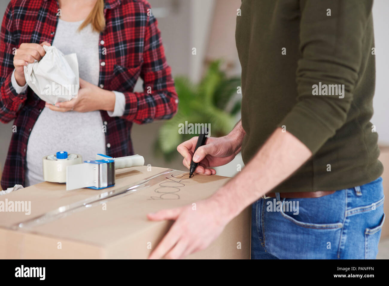 Couple moving house packing and labelling cardboard boxes - Stock Image