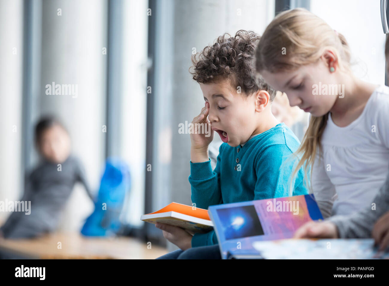Tired schoolboy with book in school - Stock Image